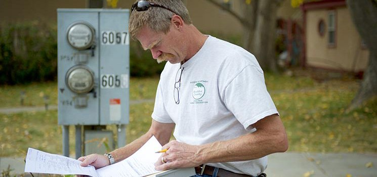 A worker reviews paperwork while standing next to a control box.