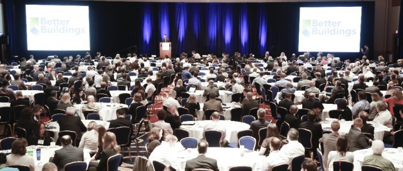 Large group of people in a convention hall or auditorium watching a presentation.