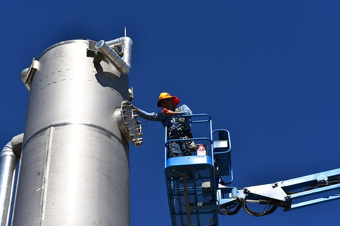 An employee with Bechtel National works on one of the non-radioactive liquid waste disposal (NLD) system's air stripper towers at WTP.