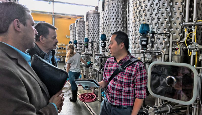 LLNL researcher Congwang Ye visits with professors at UC Davis to see their pilot-scale winery and brewery and learn about fermentation tank operations.