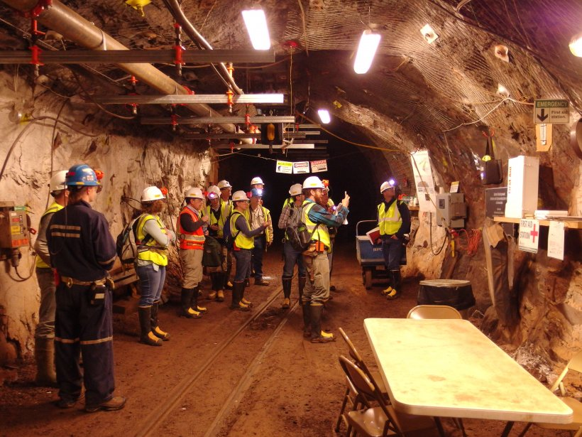 Photo of a group of workers in hard hats in an underground tunnel.