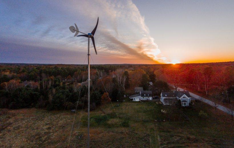 A distributed wind turbine neare a home at sunrise.