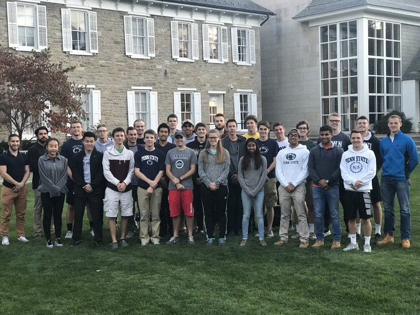 The Pennsylvania State University Collegiate Wind Competition team stands on the grass in front of their university.