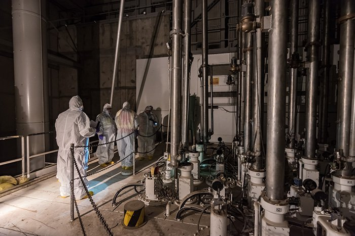 Workers inspect vertical safety rods in the K East Reactor above the reactor core. Control rods were used to regulate plutonium production during the Cold War.