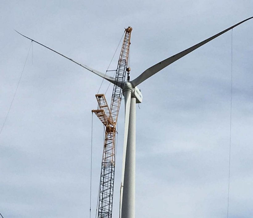 Photo of a wind turbine with crane propped up against it.
