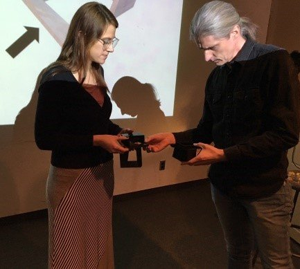 Photo of two people in a presentation room, with a screen behind them, examining objects for a project.
