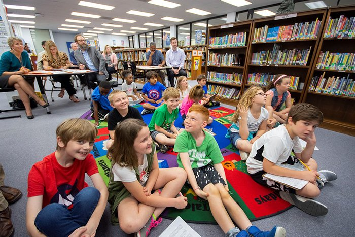 Students eagerly wait their turn to share what they've learned.