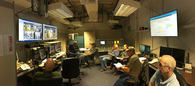 Workers in the control room monitor the beginning of transferring sludge out of the K West Basin on the Hanford Site.