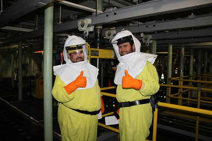 Shay DeWitt, nuclear chemical operator, left, and Mike Garza, field work supervisor, give a thumbs-up during the first day of sludge retrieval on June 12.