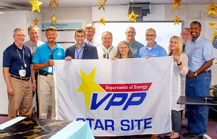 Employees from the Oak Ridge Office of Environmental Management and North Wind Solutions hold a flag that will hang at the Transuranic Waste Processing Center.