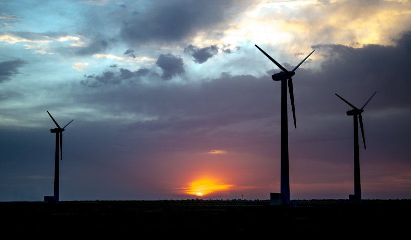 Photo of three wind turbines taken with the sun setting behind them.