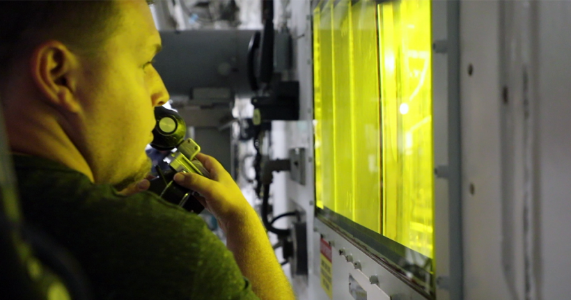 A researcher at ORNL works with a robotic arm outside of a hot cell.