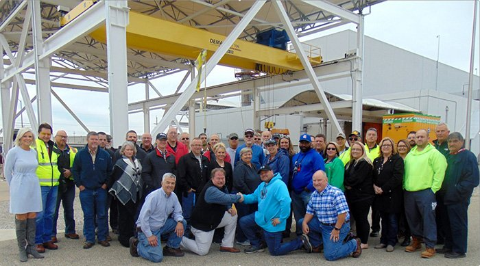 PPPO Manager Robert Edwards, shaking hands with Mid-America Conversion Services Union Safety Representative Jeremy Bates & personnel at EM's Portsmouth Site for a group photo to commemorate all seven DUF6 Conversion Project production lines in operation.