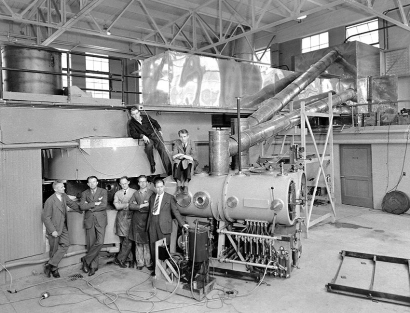 Posing with the newly completed 60-inch cyclotron in the Crocker Laboratory are (left to right) Donald Cooksey, Ernest O. Lawrence, R. Thornton, W. Salisbury and J. Backus and (on top) L. Alvarez and E. McMillan.