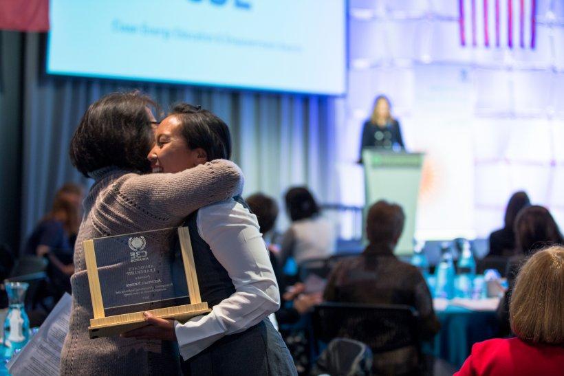Award recipients hug at the C3E Women in Clean Energy Symposium.