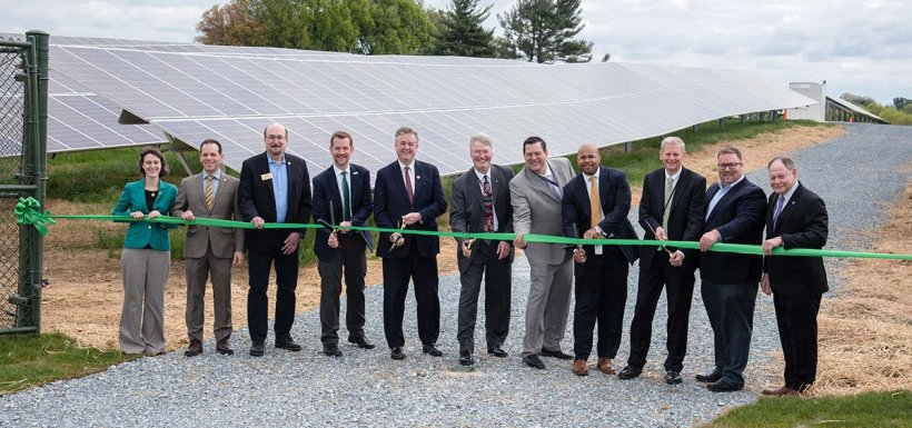 Image of 10 men and one woman holding a green ribbon with three men in the middle holding scissors to cut the ribbon.