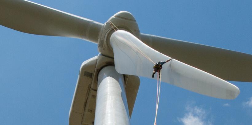 person rappelling down a wind turbine.