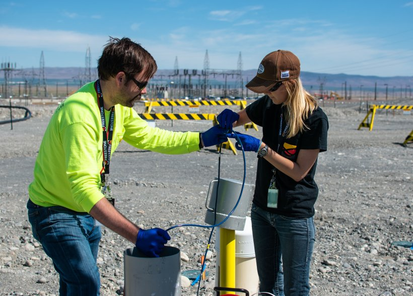 Freestone Environmental Services geologists Zack McGuire, left, and Lindsey Getchell deploy a sensor the firm developed under the Small Business Innovation Research Program.