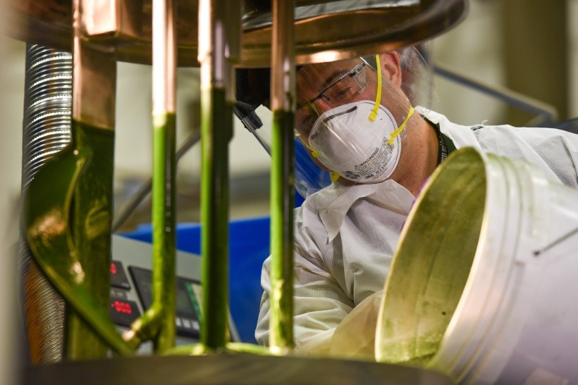 A lab tech working in a lab with a bucket of algae