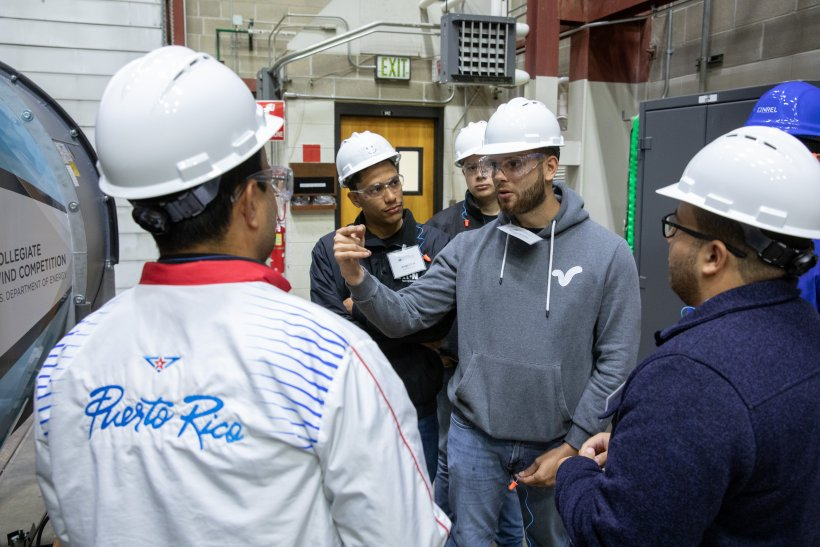 Five students in safety gear stand in a huddle next to a wind tunnel.