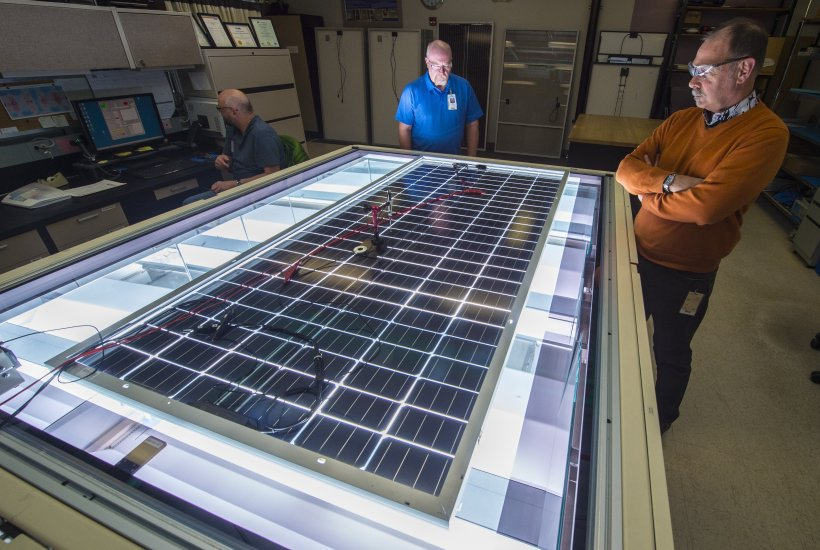 Allen Anderberg, Steve Rummel, and Dean Levi of NREL's Cell and Module Performance group measure the power output of a PV module on NREL's solar simulator. Photo by Dennis Schroeder.