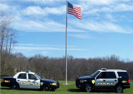 Photo of two police cars and an American flag behind.