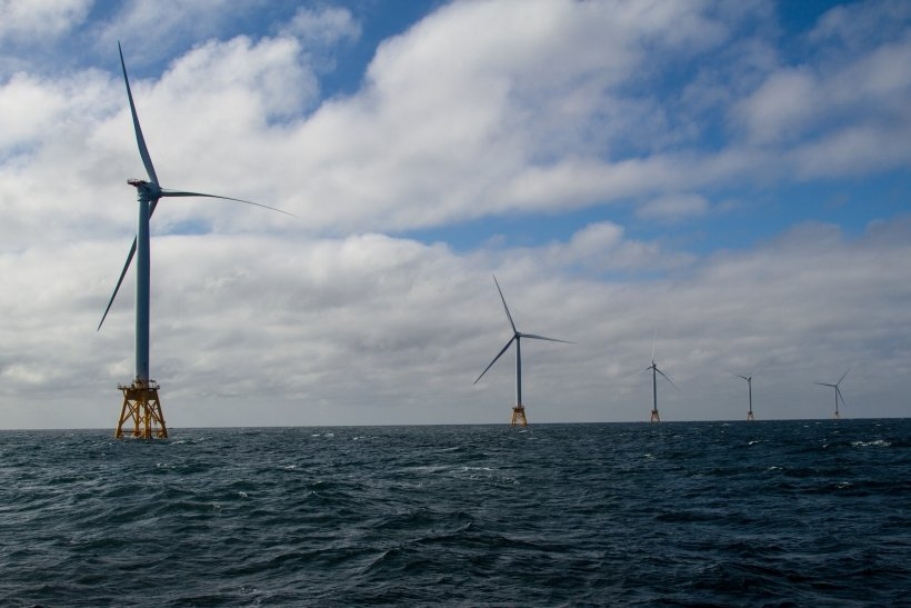 A string of offshore wind turbines in the ocean.