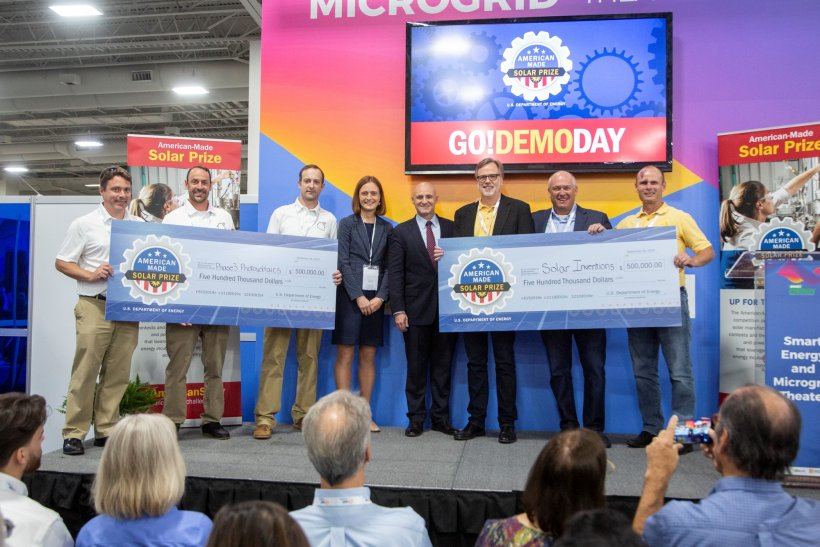 Three winners from Phase 3 Photovoltaics and three from Solar Inventions hold up mock checks while Becca Jones Albertus of the Solar office and Assistant Secretary Daniel Simmons stand in the middle.