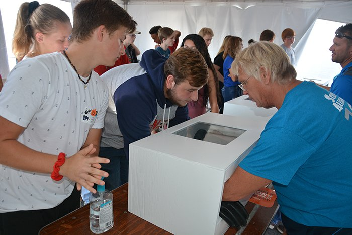 Dan Minter with EM contractor Portsmouth Mission Alliance, right, works with students during a glovebox demonstration at EM's Science Alliance event.