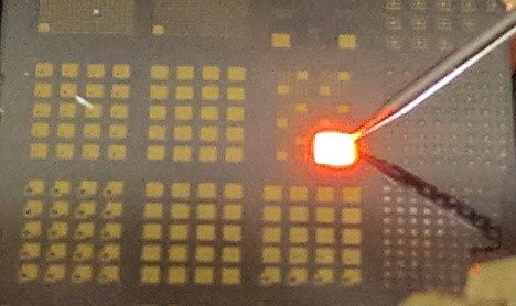 Photo showing light emission from an unpackaged AlInP LED on a substrate.