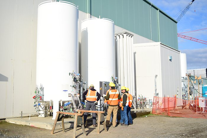 Hanford Waste Treatment and Immobilization Plant (WTP) workers inspect two bulk liquid argon storage tanks that are part of the liquid gas storage system at the WTP Analytical Laboratory.
