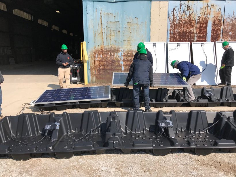 Program participants readying solar panels for shipping.