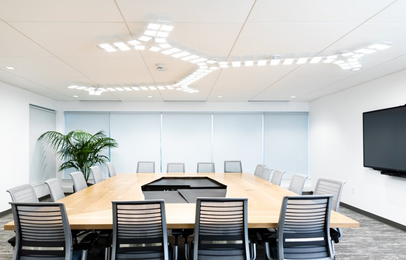 Large conference room table in an office, with empty chairs all around.