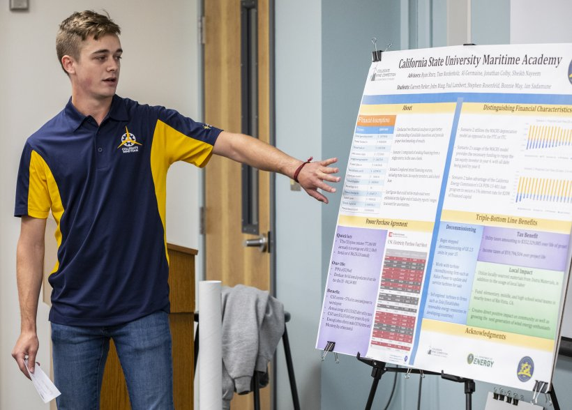 A young man gestures toward a presentation poster.