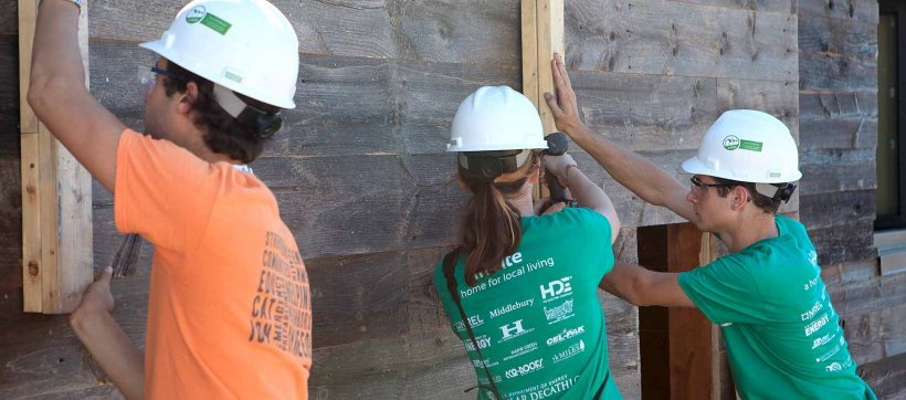 Three student team members in hard hats working on a Solar Decathlon house.