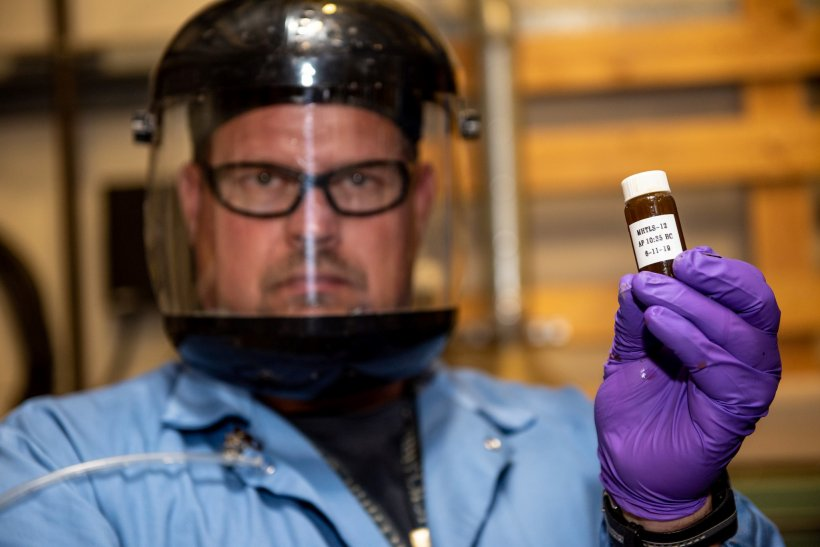a photo of a scientist holding up a small glas bottle.