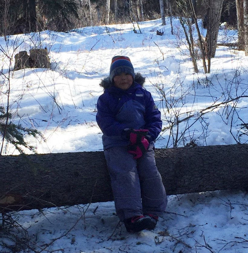 Young girl standing in a forest full of snow.
