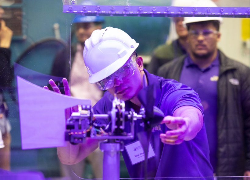 A student installs his team's turbine in a wind tunnel for a test during the CWC 2019 Technical Challenge.