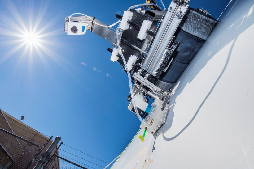 Crawling robots and drones with infrared cameras against a blue sky and sun.