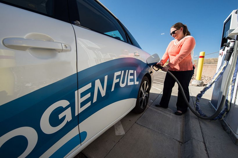 Woman filling up a hydrogen fuel vehicle.