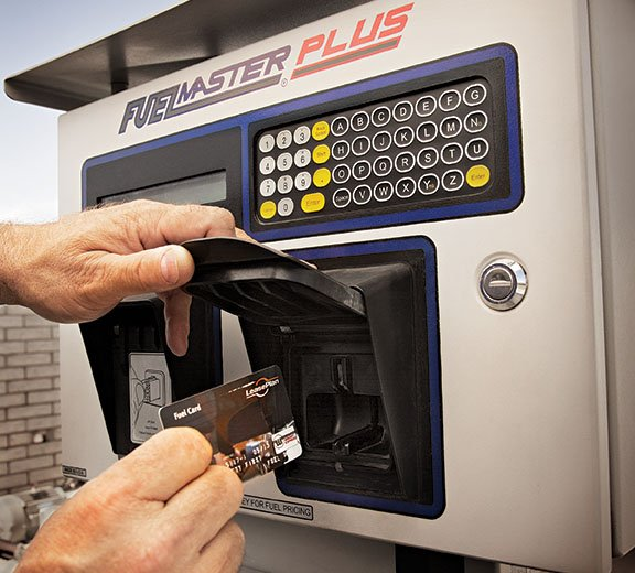 Hand inserts a credit card into a FuelMaster Plus payment machine.