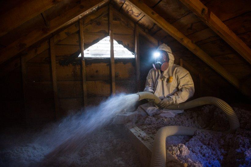 Weatherization worker insulating an attic.