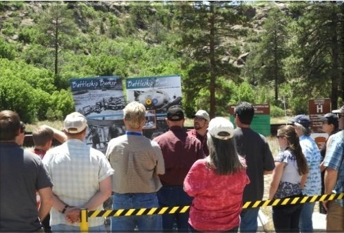 In this 2018 photo, visitors to the Pajarito Site at Los Alamos learn about Manhattan Project history. The site includes the Pond Cabin, Battleship Bunker, and Slotin Building used by scientists developing the plutonium bomb.
