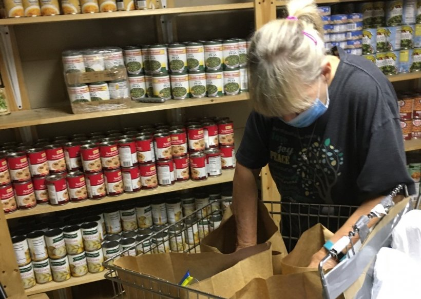 Lighthouse Community Food Bank volunteer Beverly Conner loads groceries into sacks to distribute to Ballard County families.