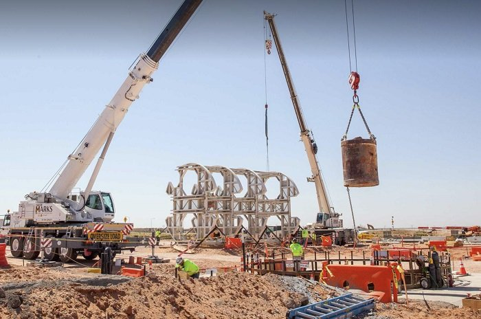 A bucket of excavated dirt is lifted out of the utility shaft that is being excavated at the Waste Isolation Pilot Plant.