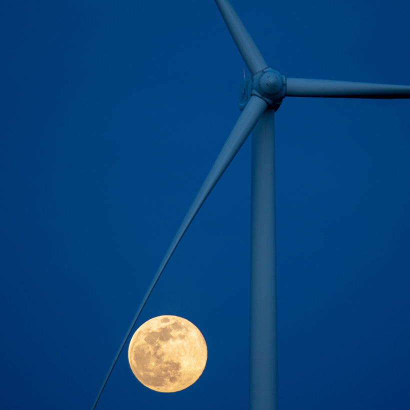 Wind turbine at night against the pink moon.