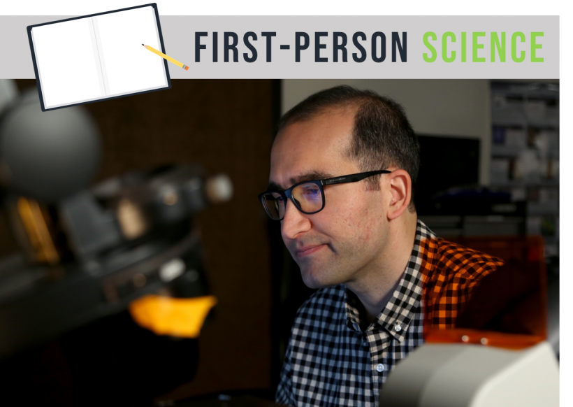 Man with a checked shirt on sitting in a laboratory next to a computer and in front of a microscope.