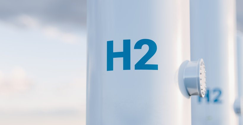 Tall white hydrogen tanks with H2 painted in blue on the front.
