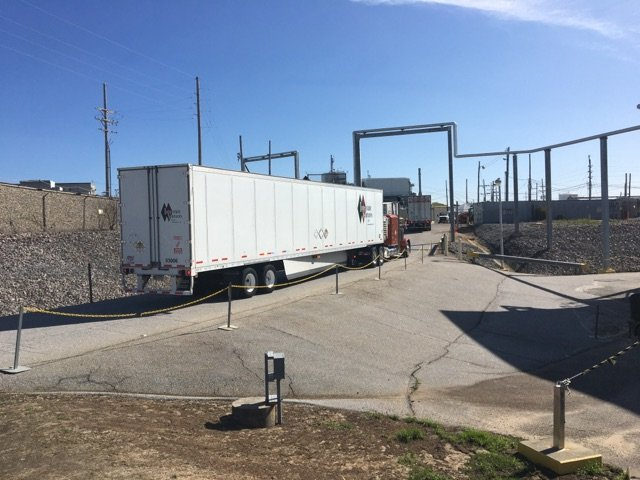 A truck containing a small amount of Defense Waste Processing Facility recycle wastewater departs a loading area at the Savannah River Site.