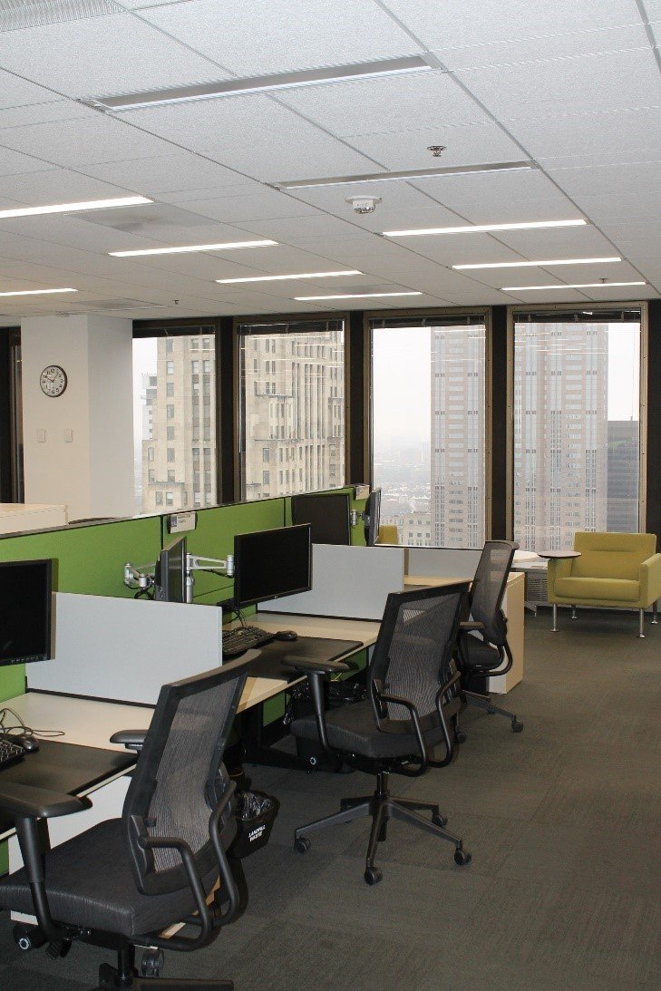 Office building cubicles with integrated lighting above them.